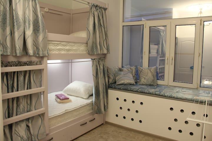 Кровать в общем 6-местном номере с большим окном