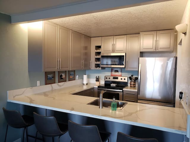Well equipped stainless steel kitchen opens to family room with seating for 4 at the bar.