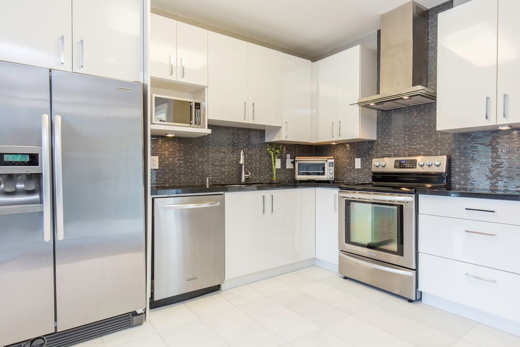 Fully stocked kitchen with stainless steel appliances.