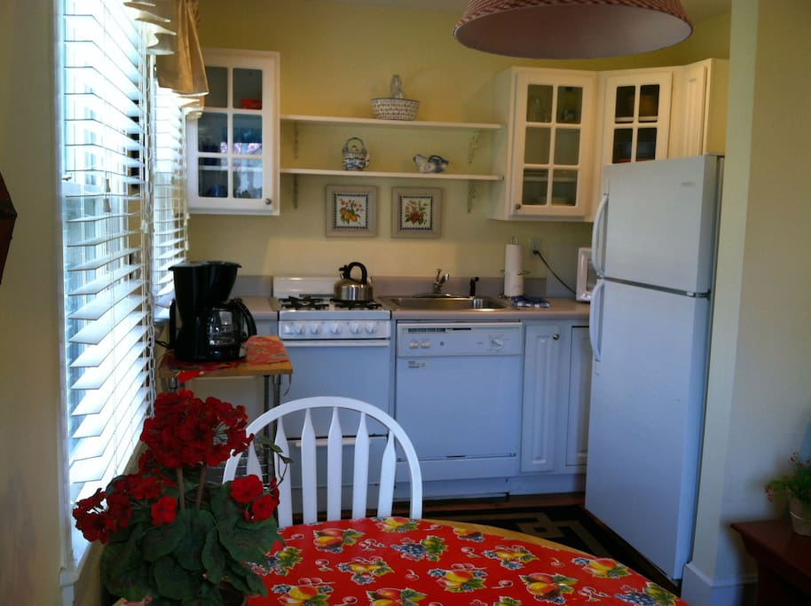 View of fully equipped galley kitchen, table and chairs