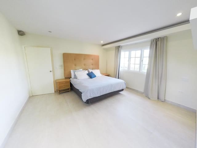 Master bedroom with kingsize bed, master bathroom and walk-in closet.