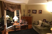 Living Room with television, two chairs and a love seat