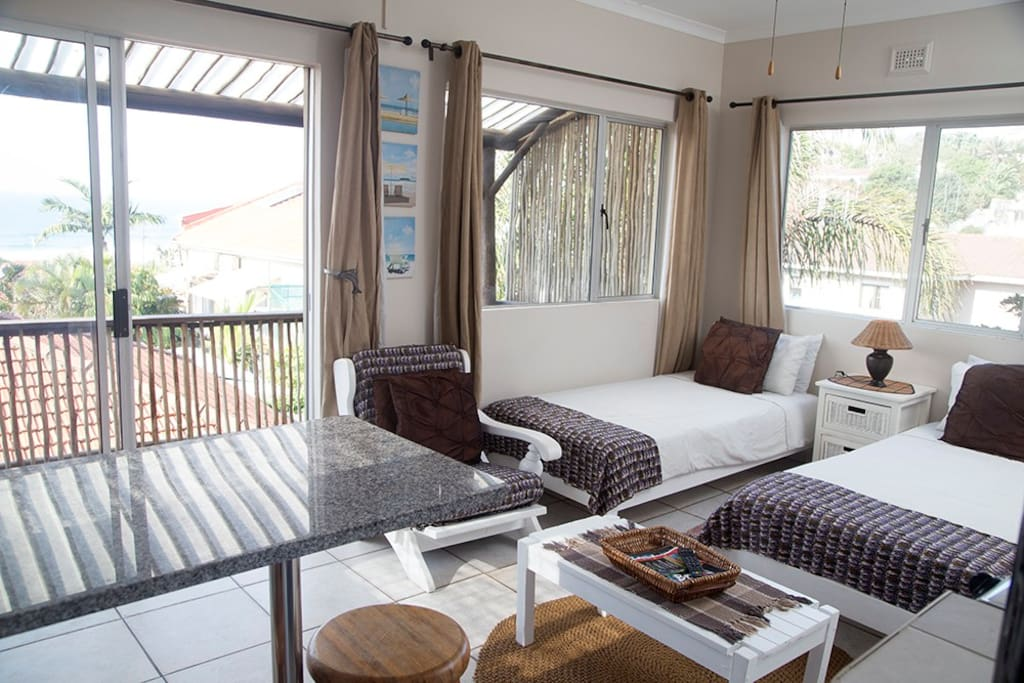 Main living area as seen from entrance :  2 single beds, deck and kitchenette with fantastic views of the sea