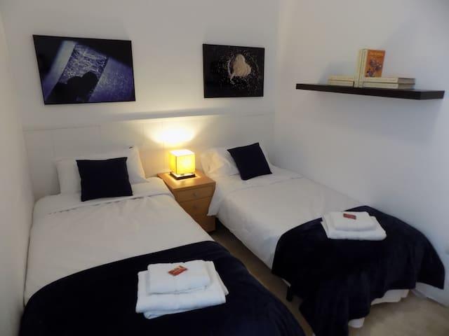 """Dormitorio nº 3 con todo lo necesario para dos personas. Las fotografías también corresponden a la exposición """"Corazonaria"""" de Ángeles Pérez.  En caso de que el número de huéspedes sea solo cuatro este dormitorio no se utiliza."""