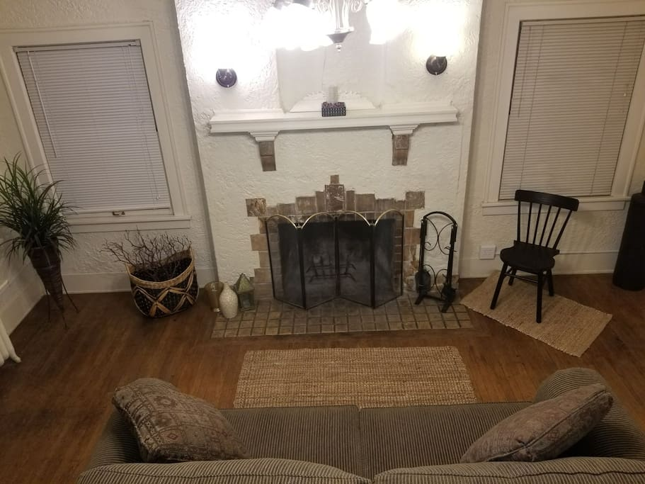 spacious charming living room with 15 foot cathedral ceilings, hardwood floors and fireplace