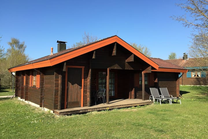 Inviting wooden bungalow with tiled stove in holiday park with a large play area