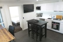 Self-contained one bedroom apartment with bedroom, large bathroom, and kitchen/dining room (with television with Amazon Fire TV for streaming).