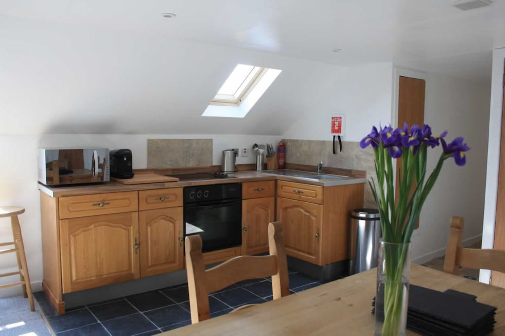 The kitchen area - sink, fridge, small freezer, cooker and hob, coffee machine, toaster, kettle, toastie maker