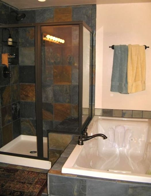 Spa like bathroom with slate tiles and walk-in shower as well as a jetted bathtub