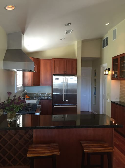 Chef's kitchen with Viking appliances, and granite counters, including breakfast bar and fully stocked. Open floor plan to the living room and dining room