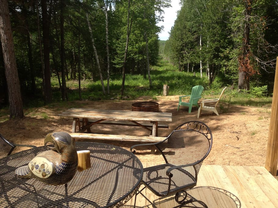Deck and eating-and-relaxing area off back of cabin overlooking forest and bon fire pit.