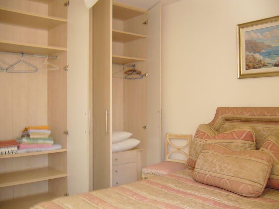 Quarto com closet e cama Queen Size.