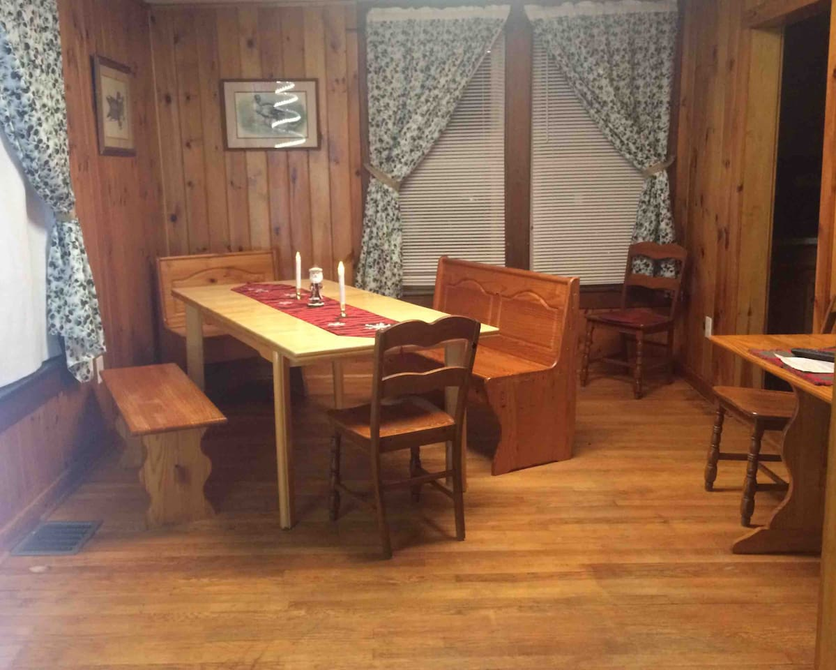 We recently added this longer dining room table,.. plenty of room for your larger group.  This photo shows our original , reclaimed hardwood floors and knotty pine walls which are also throughout our ADIRONDACK Penthouse.