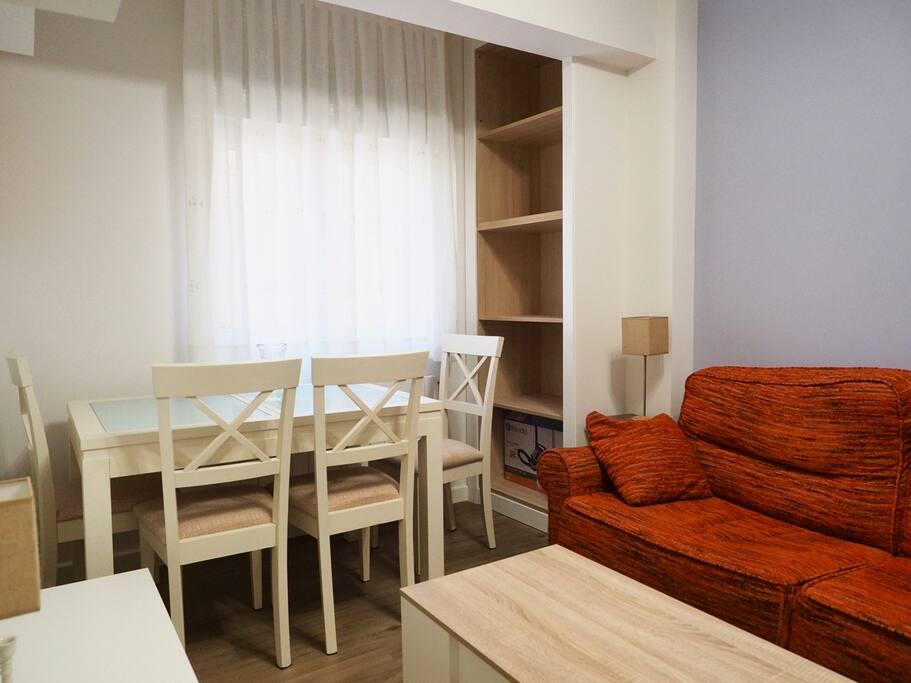Salón acogedor con televisión, sofá y mesa