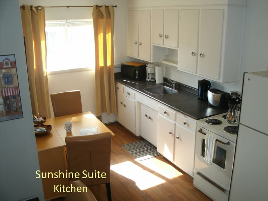 Fully equipped kitchen with dishes, cutlery, pots, pans, oven, fridge, expandable table with two chairs, microwave, toaster, electric kettle, and coffee maker.