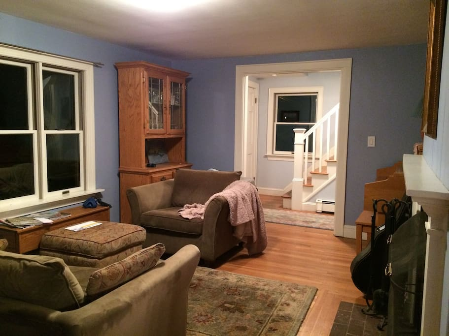 Living room / music parlor with couch and chair  and ottoman with fireplace, piano and guitar