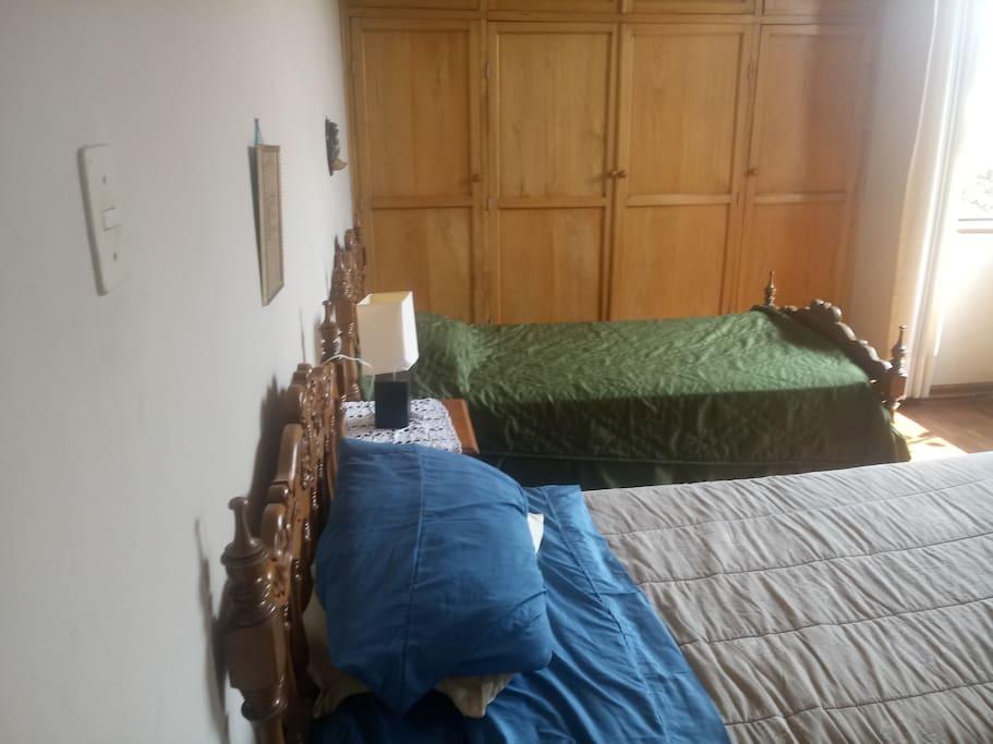 Dormitorio con dos camas de plaza y media tocador y closet