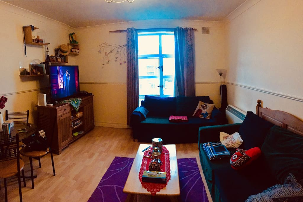 Spaceful living room with dining table, SmartTV and sofa with a view to the Liffey river.