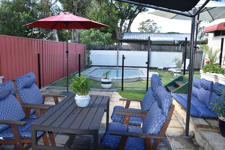 Outdoor Shaded Dining overlooks pool area through glass pool fencing