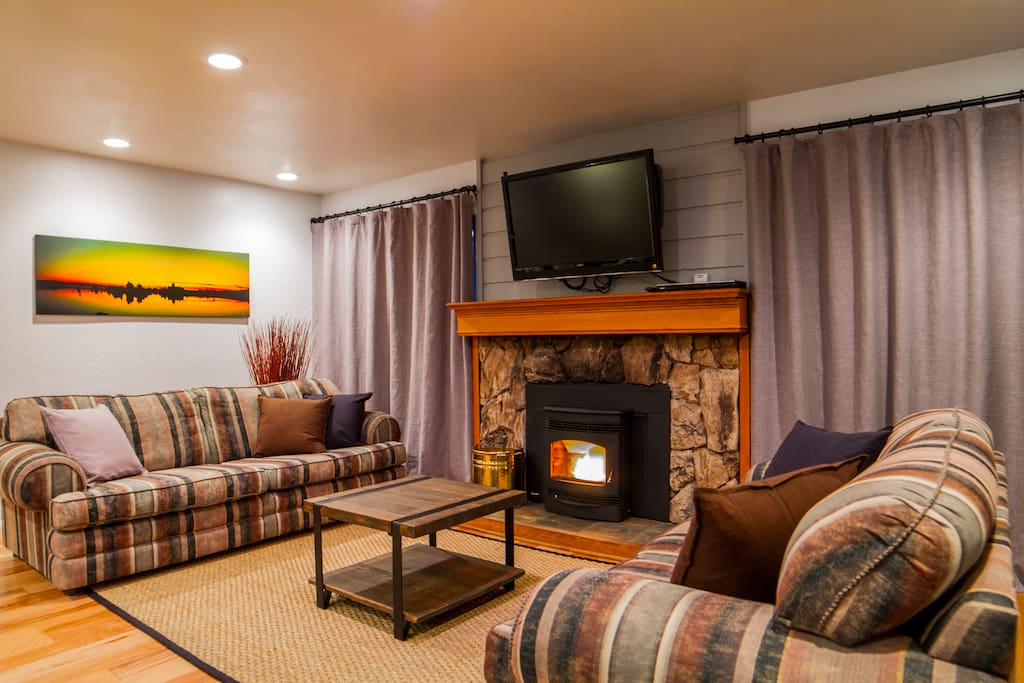 Spacious lounge room with wood floors and fireplace