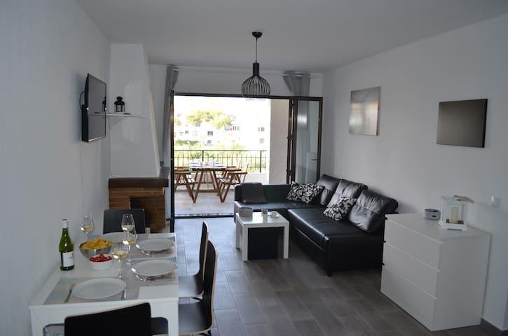 nett eingerichtetes Wohnzimmer mit Blick auf die Terrasse und ins Freie