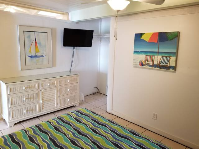 Incredibly bright & fresh smaller bedroom with flat screen for TV at night & patio door out to deck