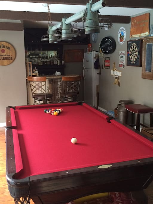 Play pool and darts, while watching the pregame shows and lounging at the bar. A sliding glass door to the left looks outside at the pool, a firepit, and smoker, and a ping pong table.