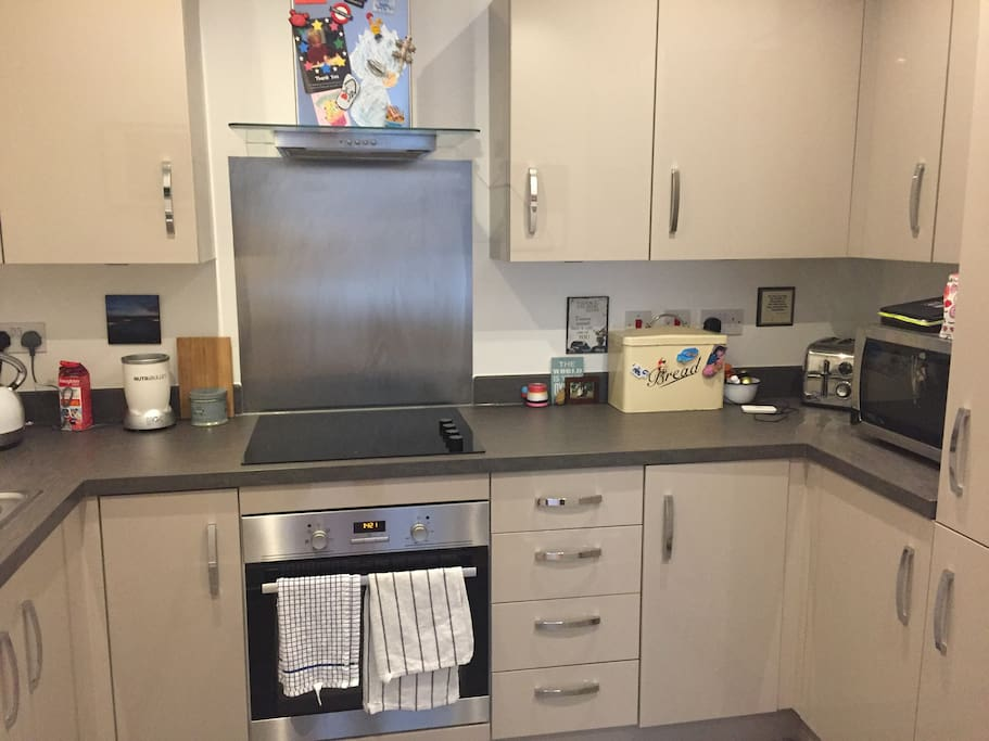 Kitchen with dish washer, electric oven and hob, microwave, fridge freezer