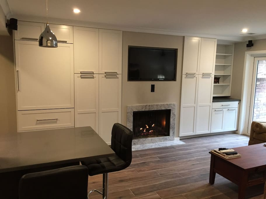 Gas fireplace and Sub Zero fridge behind custom cabinets