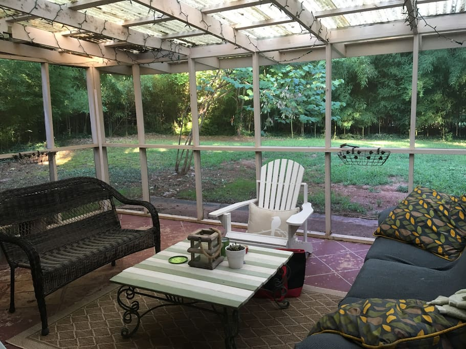 Screened in porch out back with mounted tv (cable), view of private backyard, perfect for enjoying sunsets and morning coffee