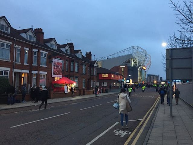 View down Sir Matt Busby Way featuring MUST HQ with the matchday stall lit up outside and the stadium in the background