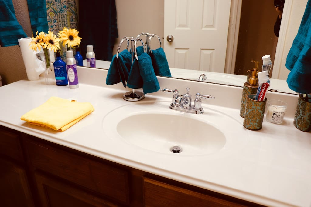This full bathroom contains, towels, shampoo, body wash, toothpaste, hand soap, hairdryer, hand lotion.