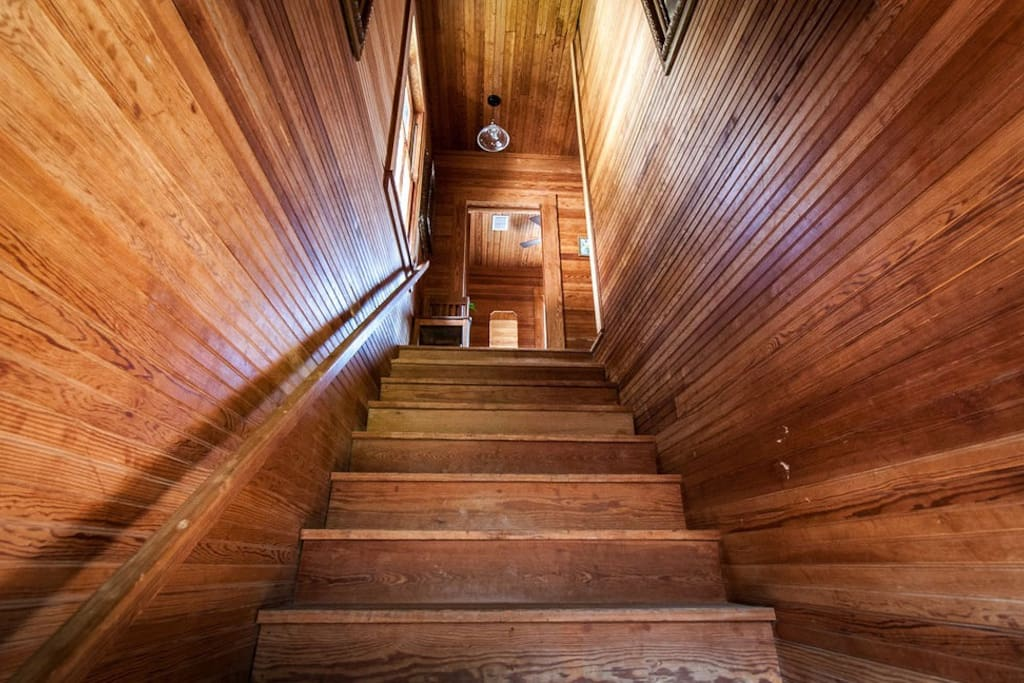 The stairwell in the carriage house has a handrail. Bead-board covers the walls and ceilings, and the floors are long leaf pine.