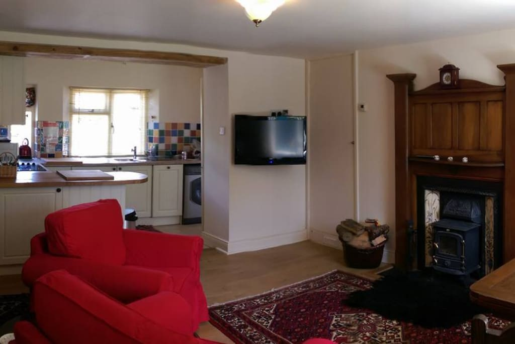 Downstairs kitchen dining room with wood burning stove and  HD tv.