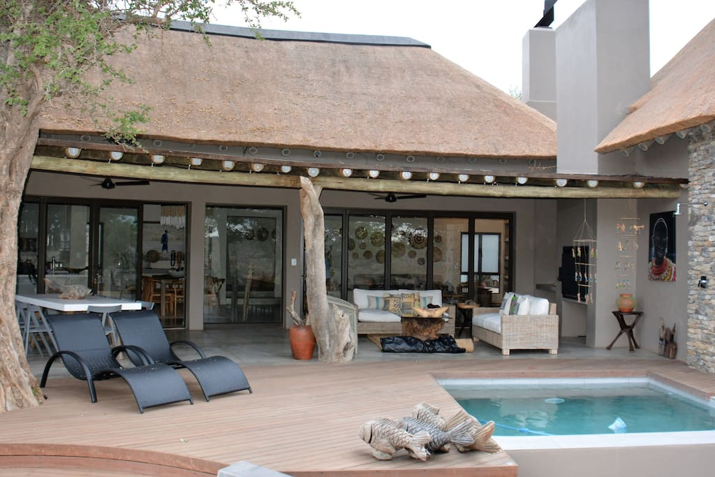 Outdoor patio, pool, outdoor dining table and lounge area.