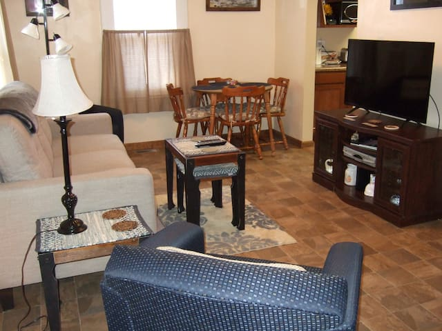 Main living/dining room, features table and chairs for dining, couch, two additional chairs, TV and work desk.