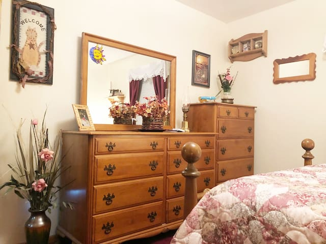 Red bedroom with full dresser and mirror.