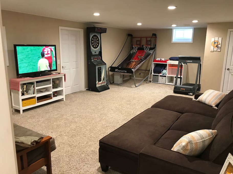 Lower level room with working treadmill, bar-style dartboard, and basketball game.