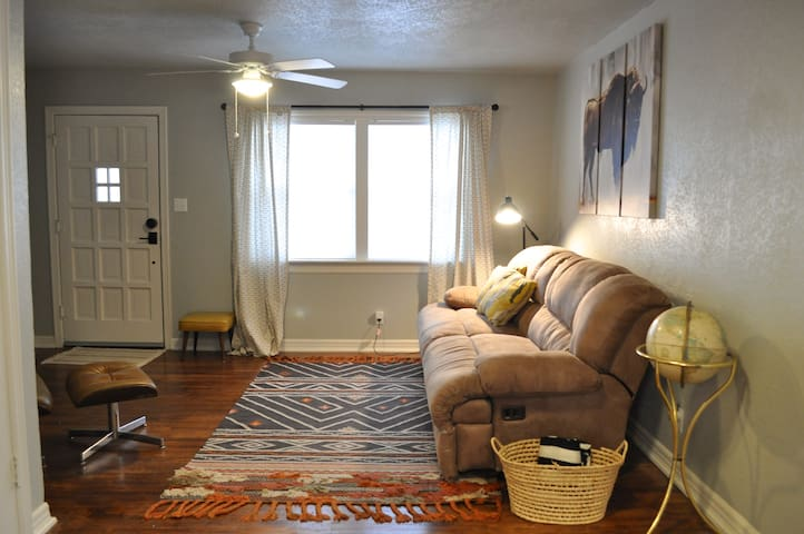Living Room: double reclining sofa, extra blankets, and additional seating. There is also a coat closet that houses a vacuum, swiffer and mop.