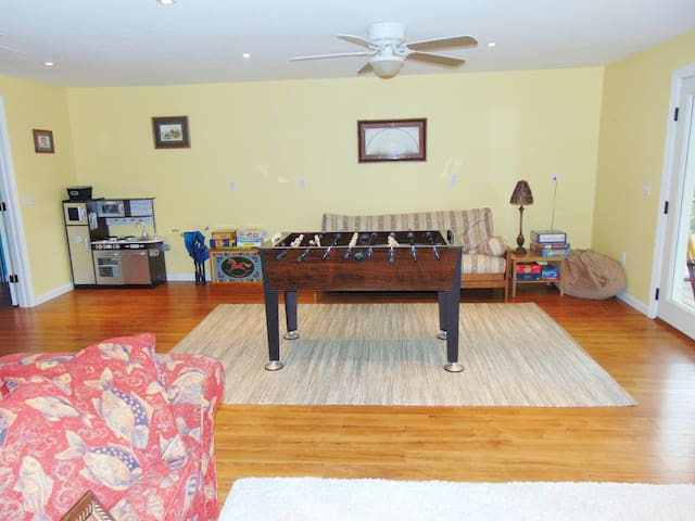 Large play room with foosball table, futon sofa and numerous children's toys.