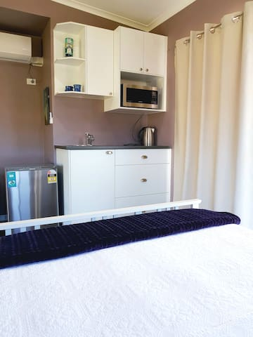 Kitchenette with bar fridge, microwave oven, toaster and kettle.