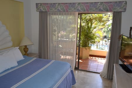 Main bedrooms with cable TV, view to the pool and gardens.