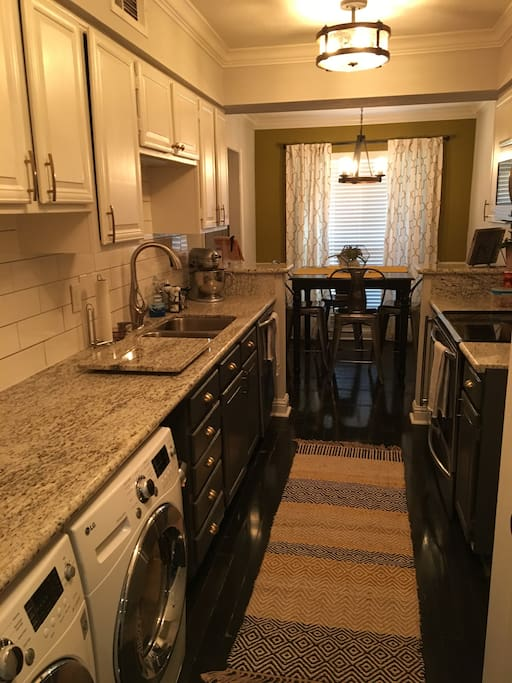 Galley kitchen includes stainless steel appliances and front loading washer/dryer.