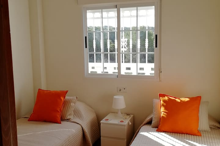 Upstairs air conditioned bedroom with 2 single beds and double fitted wardrobes. Bedside cabinet and bedside lamp. Safe for valuables. Bathroom opposite the room. Room  freshly decorated. Bed linen and towels supplied. Views to nature reserve.