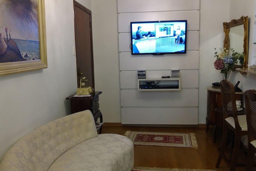 sala de estar com sofá , TV e duas cadeiras decorativas