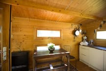 Inside our homely little Hut,  showing from L to R: eco-fireplace (runs on meths), dining table, and kitchenette.