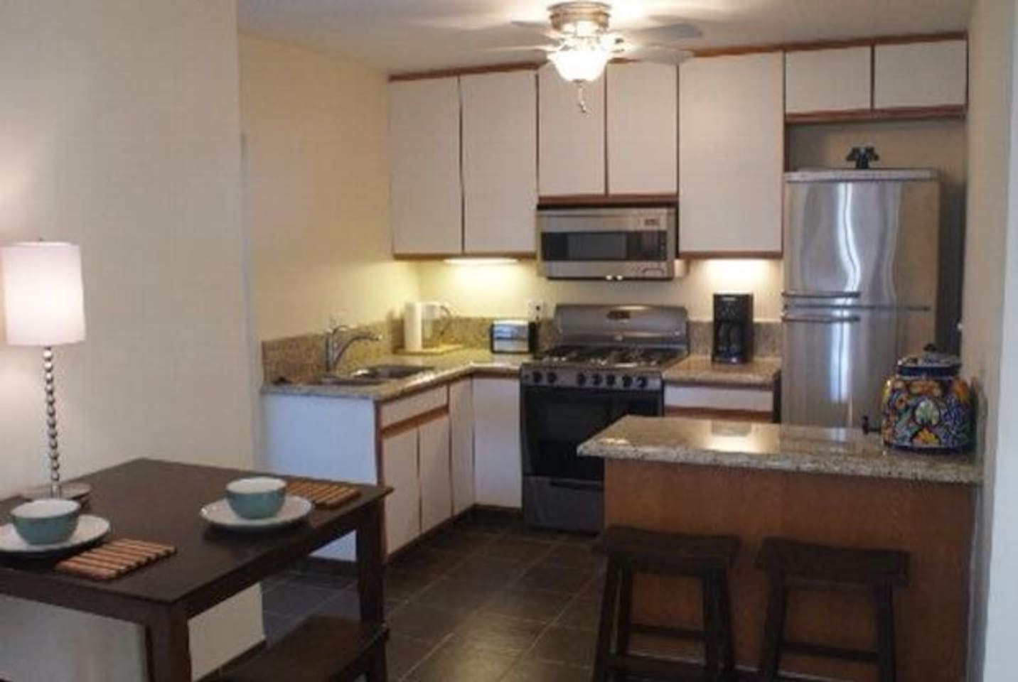 Fully equipped kitchen, breakfast bar and dining area with access to washer, dryer and roof access on the service porch.