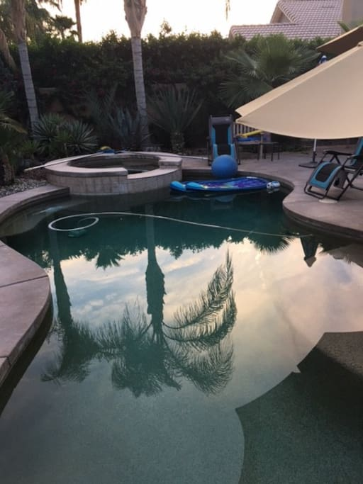 pool with lounge chairs umbrellas and patio furn