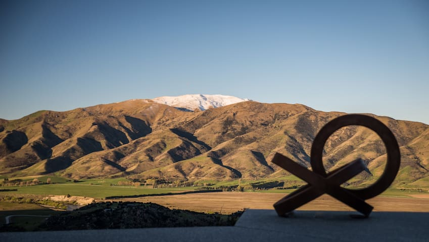 "This Corten steel ""Circles of Life"" sculpture by Auckland sculptor Neil Donaldson can be seen from all angles of the 180 degree view and is lit up at night. The folds of the mountains are echoed in the folding roof of the house."