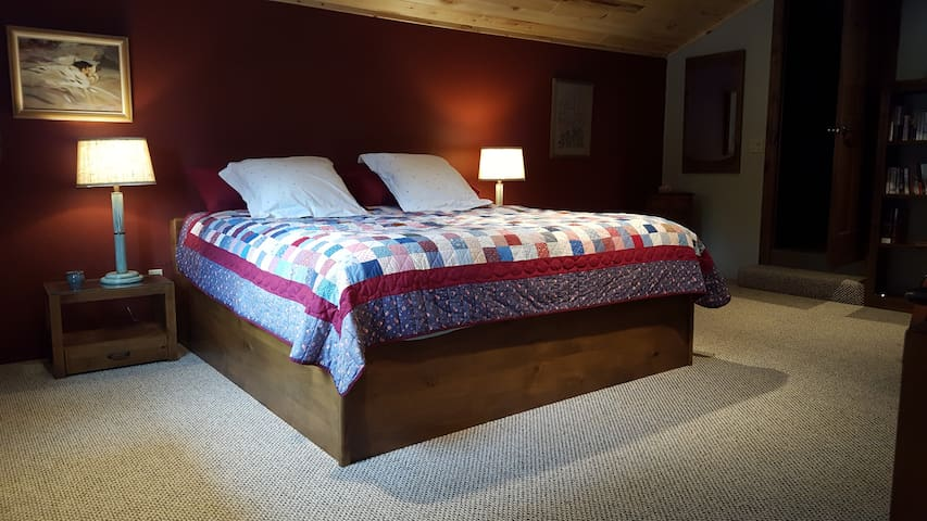 The upstairs bedroom is a loft and features a king size bed and access to the bathroom.